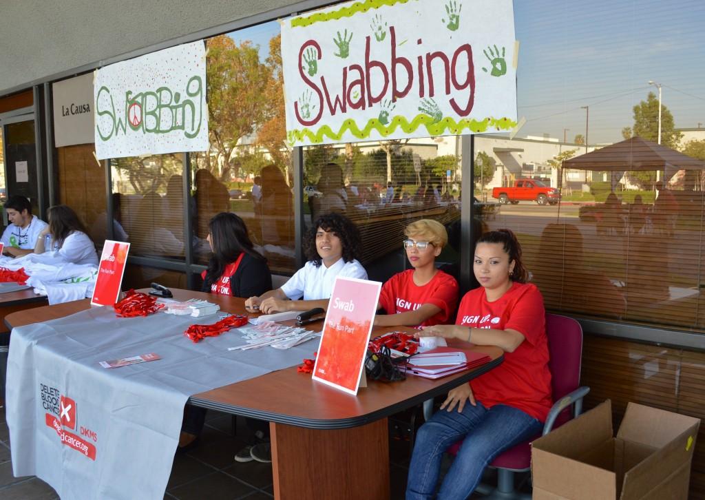 "Students at the ""swabbing"" table, assisting participants."